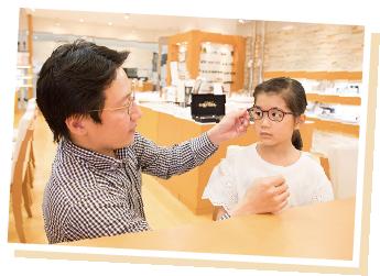 男性が女の子のメガネのフィッティングをチェックしているところ
